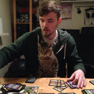 My husband playing Dominion with our cat, Kato