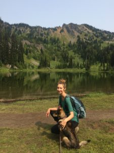 Kari kneeling with dog on a hike