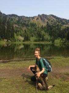 Kari kneeling with dog on a hike